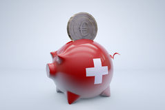 Swiss piggy bank with euro coin. A Euro coin is put into piggy bank, symbolizing Swiss bank Royalty Free Stock Photo