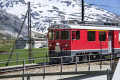 Swiss red train. Between alpine mountains Stock Photos