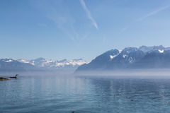Swiss riviera in spring. Serene and hazy Lake Geneva gives a surreal impression as the alps emerge in the distance Royalty Free Stock Photography