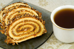 Swiss roll. On a plate and cup of tea Stock Photo