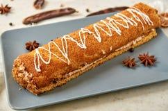 Swiss roll con crema bianca dolce sul piatto grigio decorato con il panno bianco, l'anice stellato ed i baccelli maturi della fru Immagine Stock Libera da Diritti
