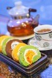 Swiss roll with hot tea on table Royalty Free Stock Photos