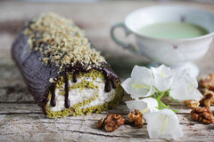 Swiss roll with matcha tea and chocolate icing filled with cream Stock Image