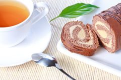Swiss roll with milk cream and a cup of tea Royalty Free Stock Images
