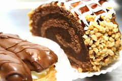 Swiss roll with nuts and chocolate and two eclairs Stock Image