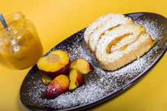 Swiss rolls stuffed with peach jam. On a serving plate Royalty Free Stock Photography