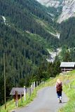 Swiss scene. View of the Swiss alps: Blonde tourist walking on road, central Switzerland Stock Photography