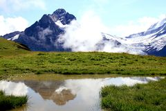 Swiss snowy mountains, glacier and lake. The high mountain Wetterhorn in the middle of Switzerland - Bernese Oberland - is mirroring in a little lake. On the Royalty Free Stock Images