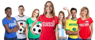 Swiss soccer fan with ball and cheering group of other fans stock photo