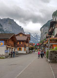 Swiss street with cars people and flags Royalty Free Stock Photography