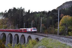 Swiss train passing by on a viaduct in the fall royalty free stock images