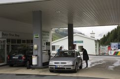 Swiss and traveler people fill oil to tank of car in petrol station Royalty Free Stock Photo