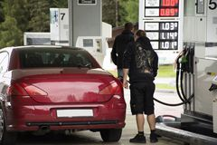 Swiss and traveler people fill oil to tank of car in petrol station Stock Photo