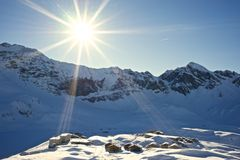 Swiss Village of Frutt in Switzerland. Winter Landscape of Sun shining on the Swiss Village of Frutt in the Snowy Alps, covered by Snow Royalty Free Stock Image