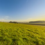 Swiss village surrounded by pastures. Swiss village surrounded by forests and plowed fields at sunset. Agriculture in Switzerland, arable land and pastures Royalty Free Stock Photography