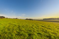 Swiss village surrounded by pastures. Swiss village surrounded by forests and plowed fields at sunset. Agriculture in Switzerland, arable land and pastures Royalty Free Stock Photo