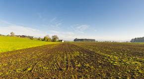 Swiss village surrounded by plowed fields. Swiss village surrounded by forests and plowed fields. Agriculture in Switzerland, arable land and pastures Stock Photos