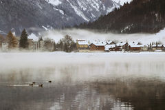 Swiss Village. View over a Swiss Village by a lake in the Alps, covered in snow during winter royalty free stock photography