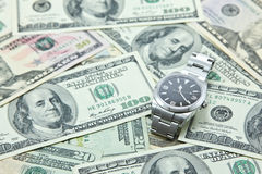 Swiss watch on pile of US dollar banknotes Stock Photo