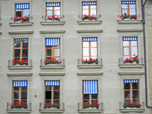 Swiss Windows. Apartment building windows in Bern, Switzerland, with red flower window boxes and blue and white striped shades Stock Photography