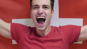 Swiss Young Man Celebrating while holding the Flag of Switzerland in Slow Motion royalty free stock image
