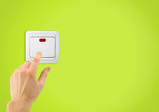 Switch. Simple light switch and hand on a green wall background Stock Photography