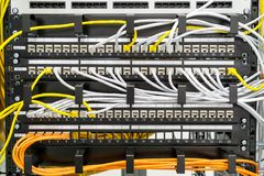 Switch and cable in an computer network. Switch ports of a computer network with yellow, white and orange cables Stock Images