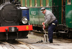 Switch. Mariefred, Sweden - May 11, 2013: A man switch track for ther train in the yard next to the steam locomotive No. 8 Emsfors that switches at the railway stock photo