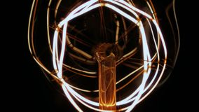 Switch on Modern Vintage Look LED light Wires Slow Motion. Static close up slow motion shot of the details within a vintage look modern LED carbon filament lamp stock footage