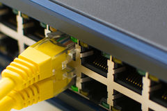 Switch Ports online. A Ethernet Network Switch with power and link with yellow cable close up Royalty Free Stock Photo