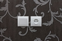 Switch and socket. On floral wallpaper Stock Photography