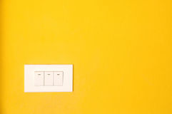 Switch on yellow wall Stock Photo