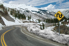 Switchback Road and Sign. A sign warns of repeated sharp turns ahead on a mountain road in southwest Colorado stock photo