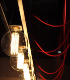 Switched electric bulbs and red wires. Hot glass of switched on electric lamps connected with red cables Stock Photo