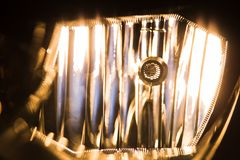 Switched on lamp in headlight closeup royalty free stock images