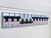 Switches in electrical fuse box. Many black circuit breakers in a row in position ON and three switch in position OFF. Power contr stock photo
