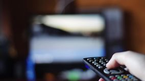 Switching channels on your TV remote control. Man lying on the sofa (bed) Press the button on the TV remote aimed at the TV. switches channels stock video footage