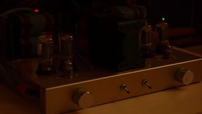 Switching off a vintage tube valve hi-fi music pre amplifier. Turn off power of tube amplifier. Locked low key. Close up stock footage