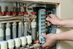 Switching signal wires in the home`s heating system control. Electrician`s hands are inserting wires in a switch for thermostats and servo drives valves in a stock images