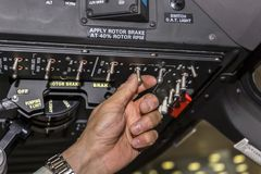 Switching tumblers by pilot. In the cockpit of the helicopter. Focus on hand Royalty Free Stock Photo