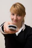 Switching the TV. Young woman with remote control Stock Photos