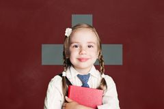 Switzerland concept with little girl student with book against the Swiss flag background royalty free stock images
