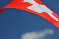 Switzerland flag with fabric structure against blue sky Stock Photography