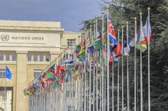 Switzerland; Geneva; March 9, 2018; Two rows of the United Nations member states flags with the United Nations Office in Geneva i. N the background royalty free stock photography