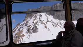 Window view of a Moving Mountain Train on the Snowy Switzerland Alps. Montreux City. SWITZERLAND, GENEVA , MAY 13, 2019: Window view of a Moving Mountain Train stock footage