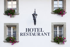 Switzerland hotel window. Lettering hotel restaurant, decorated with flower pots Royalty Free Stock Image
