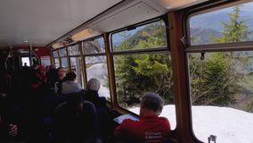 View from cabin of moving passenger mountain train with tourists at windows. Switzerland