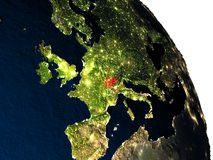 Switzerland from space. Switzerland highlighted in red on model of planet Earth with very detailed land surface and visible city lights. 3D illustration Royalty Free Stock Image