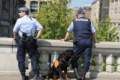 Two police men with a police dog obeying the demonstration at Ur. Switzerland: Two police men with a police dog obeying the demonstration at Urania in Zürich royalty free stock photography
