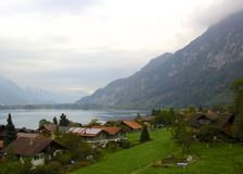 Switzerland Valley. The swiss valley on the bay is pictured here. The Alps tower over the lake and houses below. Blue water, green grass, red roofed homes. Some Stock Photo